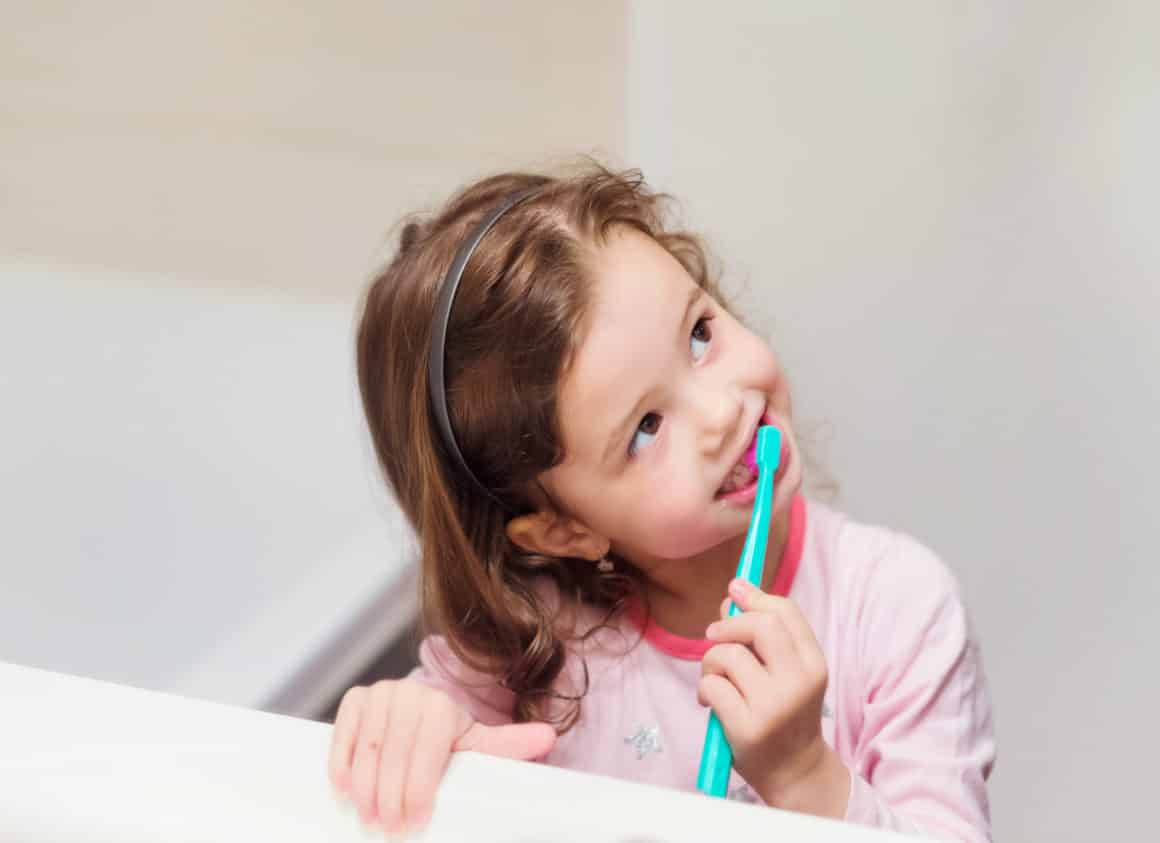 young girl brushing her teeth at home