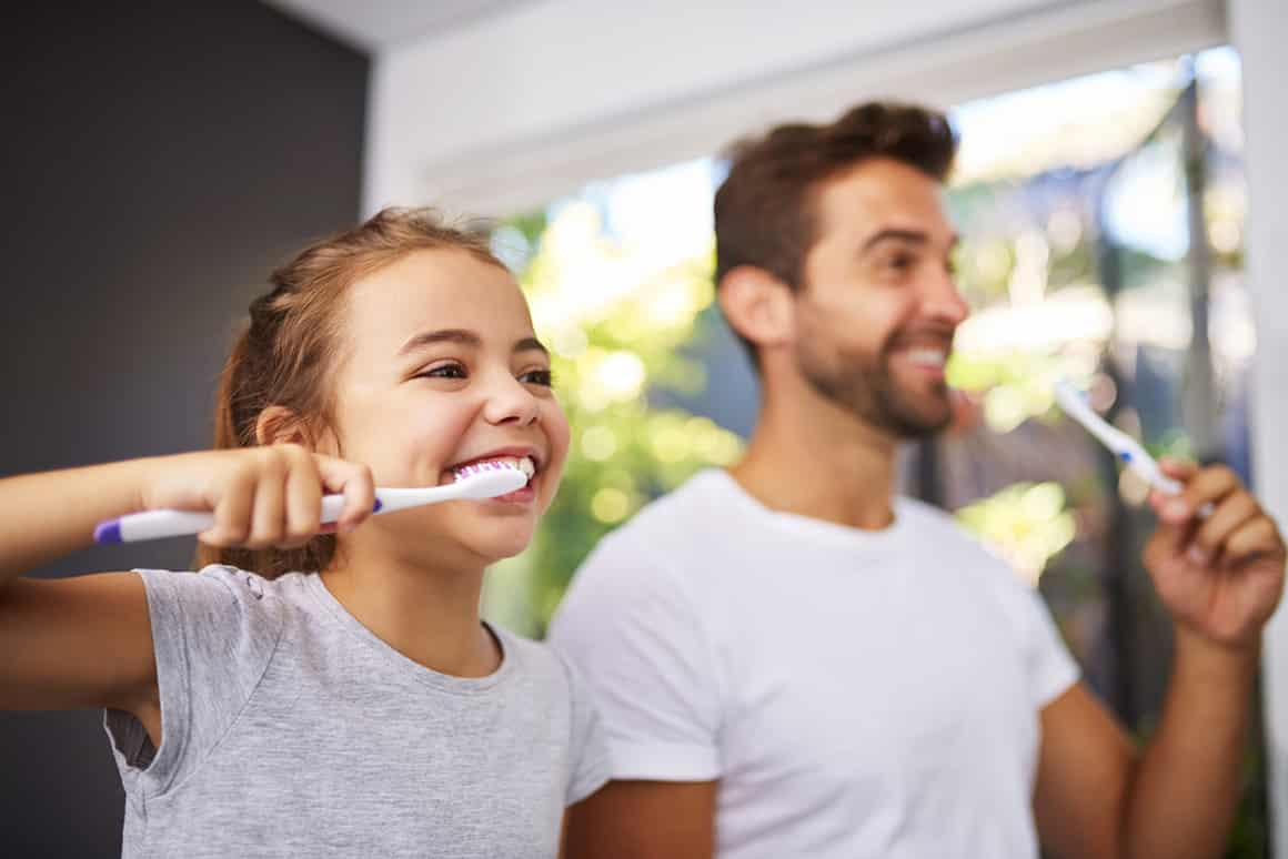 dad and daughter brushing their teeth