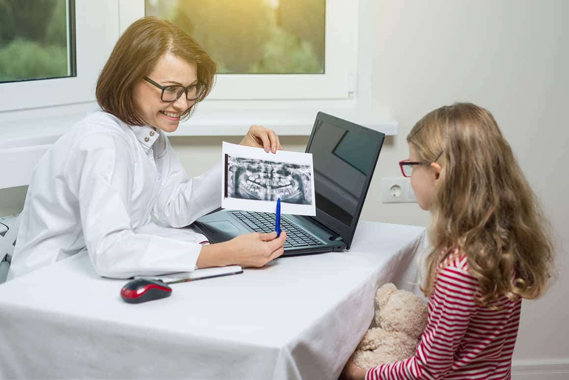 dentist showing little girl her xray at the dentist