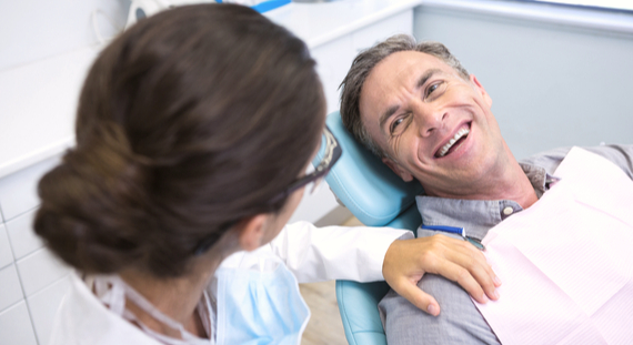 patient consulting with dentist in chair at office